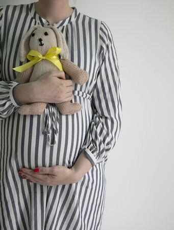 A pregnany woman holding her tummy and a bunny teddy bear