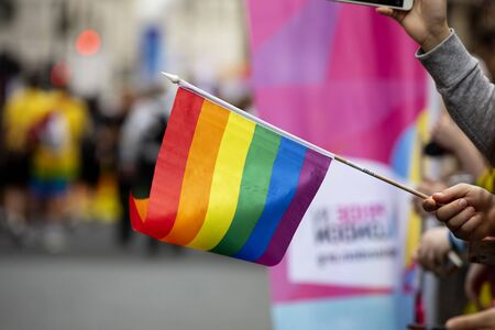 Spectators waves a gay rainbow flag at an LGBT gay pride community event