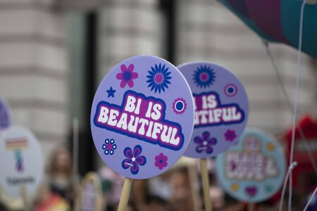 A person holding a Bi is beautiful banner at a gay pride event