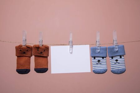 Cute baby socks with a face and blank card hanging on a clothes line Stok Fotoğraf