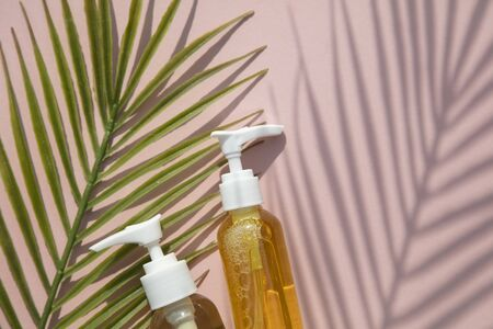 Natural cosmetic oil in a clear bottle with tropical leaf and shadow