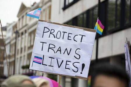 A person holding a sign reading protect trans lives banner