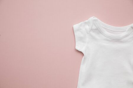 Cute baby white body suit layout on a pastel pink background Stok Fotoğraf - 131352732