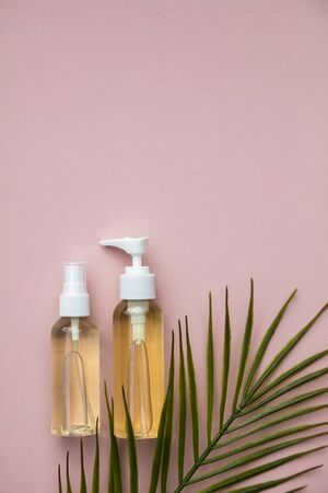 Natural cosmetic beauty products in bottles with a green palm leaf Фото со стока