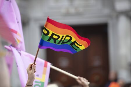 A spectator waves a gay rainbow flag at an LGBT gay pride march in London Stock Photo