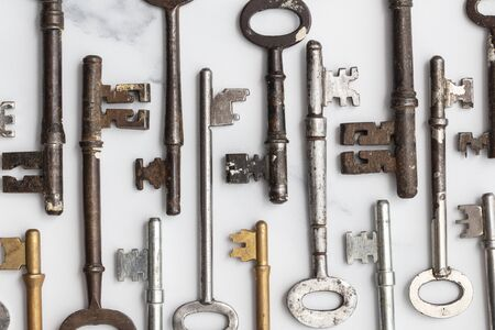 Large set of vintage keys on a plain background. Safety and security concept Фото со стока