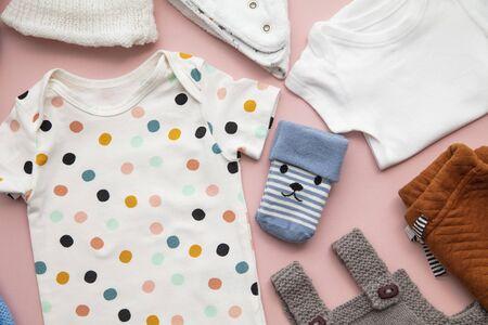 Disposition mignonne de vêtements de bébé sur un fond rose pastel Banque d'images