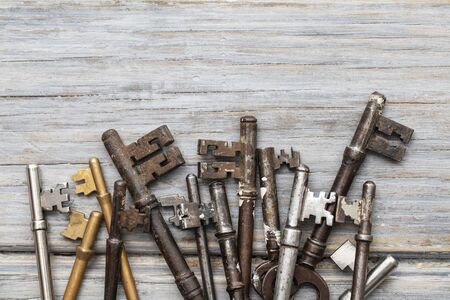 Vintage old fashioned keys on a rustic wooden background. Security concept