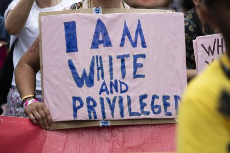 A person holding an I am white and privileged banner at a gay pride event Stok Fotoğraf