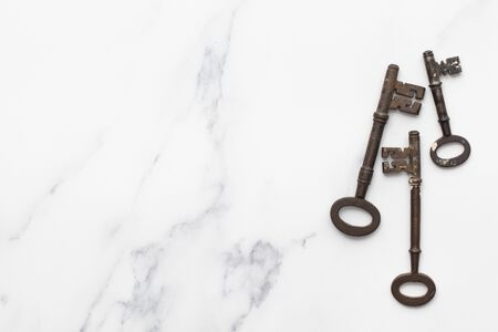 Vintage old fashioned keys on a marble background with copy space