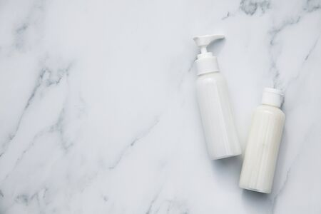 White cosmetics bottles on a marble background