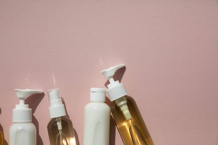 A collection of beauty cosmetic producs in clear bottles on a pink background Stok Fotoğraf