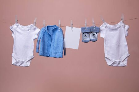New born baby grows, jumpers, socks hanging on a clothes line against pink