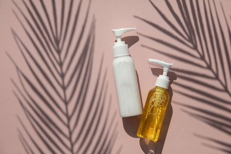 Cosmetic products in bottles on a pink background with tropical palm leaf shadow Stok Fotoğraf
