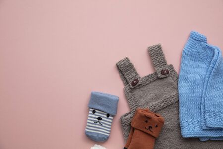 Cute handmade knitted baby clothes layout on a pastel pink background Stock Photo