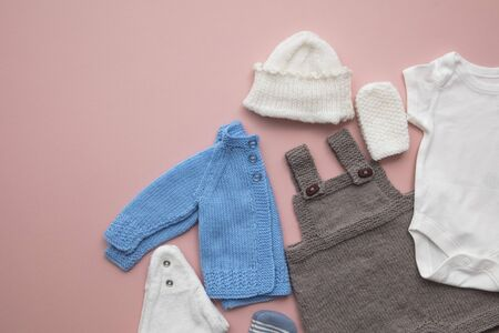Cute baby clothes layout on a pastel pink background