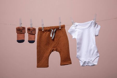 Cute baby outfit hanging from a line against a pink background Stok Fotoğraf - 131352385