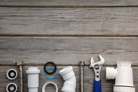 Plumbing tools, pipe and fixings on a rustic wooden background. Home improvement Imagens