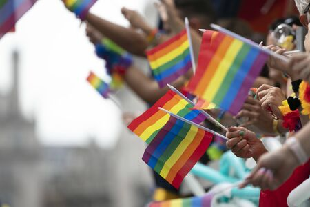 Gay pride, LGBTQ rainbow flags being waved in the air at a pride event Banco de Imagens