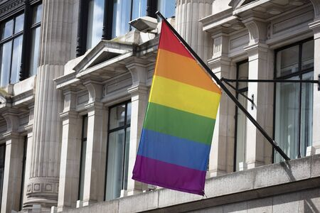 An LGBT gay pride rainbow flag hangs from a building Banco de Imagens