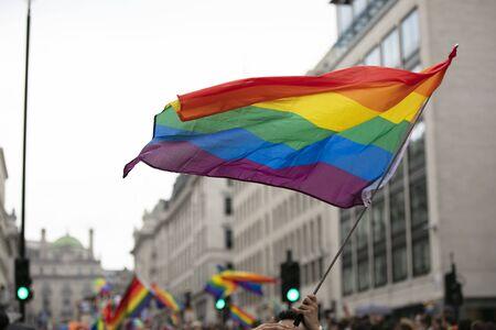 Gay pride, LGBTQ-regenboogvlaggen die in de lucht worden gezwaaid tijdens een Pride-evenement