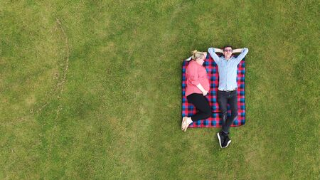 Aerial view of a pregnant woman and partner relaxing in a park