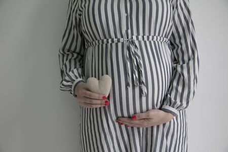 A pregnant woman holding a heart shape in front of here baby bump Stock fotó