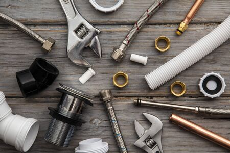 Plumbing layout. Tools and acessories on a wooden background