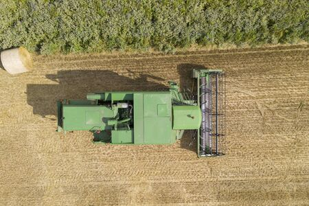 Aerial view over a green combine harvester in a farm field