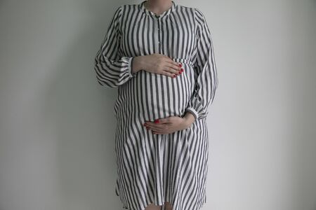 A pregnant woman holding her baby bump stood against a plain background Stock fotó