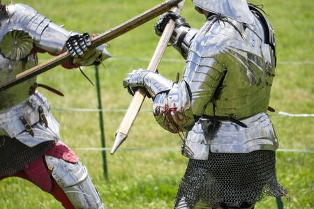 Two medieval knights in armour battle with weapons