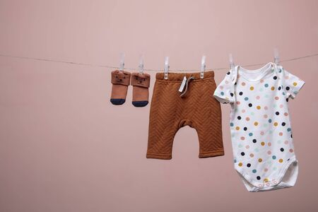 Cute baby outfit hanging from a line against a pink background 版權商用圖片