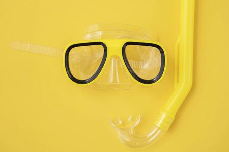 A yellow snorkel and diving mask on a yellow background. overhead lay flat