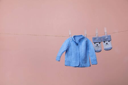 knitted new born baby jumper and socks hanging on a clothes line against pink