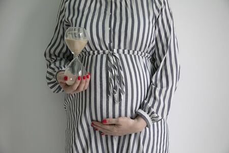 Pregnancy due date concept. Woman holding prgnant belly with an egg timer Stock fotó