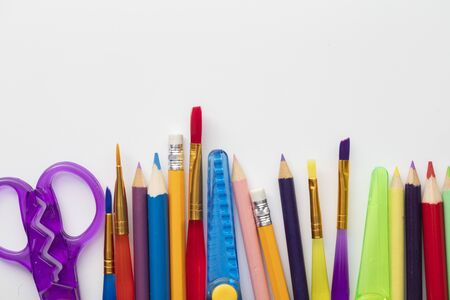 Row of school art and craft supplies on a white background