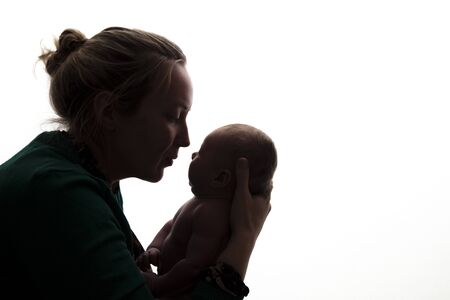 Silhouette of a mother holding her newborn baby