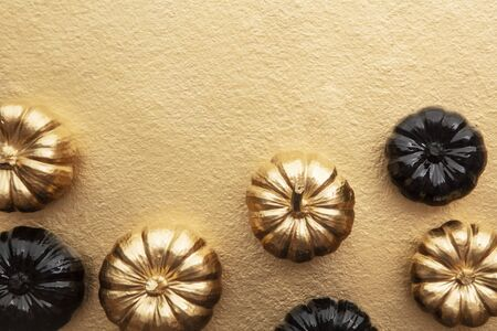 Luxury gold and black autumn pumpkin flat lay composition on a gold background Stock Photo