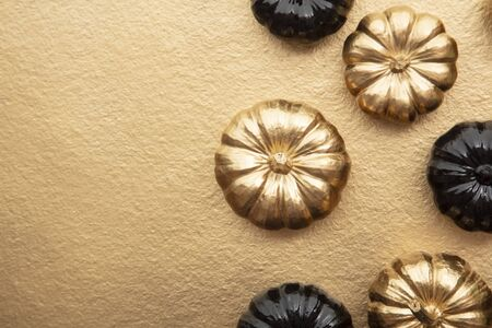 Luxury gold and black autumn pumpkin flat lay composition on a gold background Stock fotó