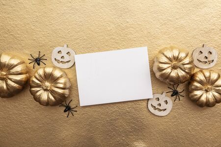 Golden thanksgiving pumpkin and blank card overhead flay lay composition