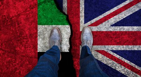 Business man stands on cracked flag of UK and UAE. Political concept Imagens