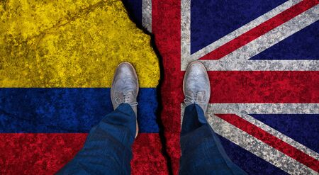 Business man stands on cracked flag of UK and Colombia. Political concept 写真素材