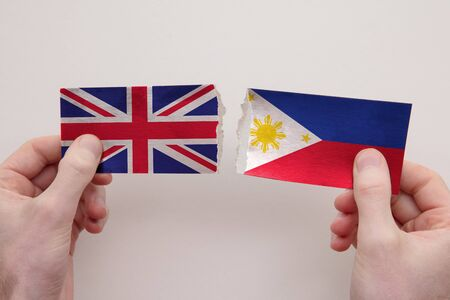 UK and Philippines paper flags ripped apart. political relationship concept