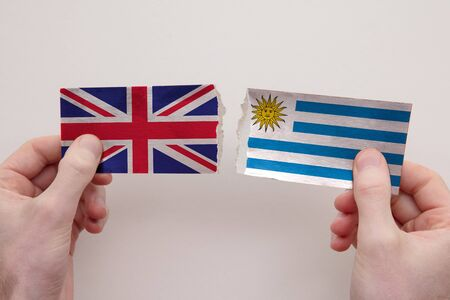 UK and Uruguay paper flags ripped apart. political relationship concept
