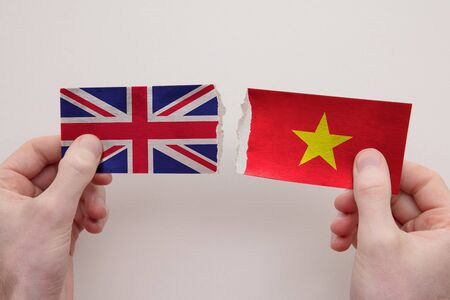 UK and Vietname paper flags ripped apart. political relationship concept