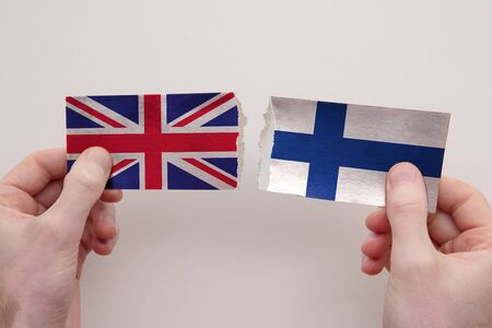 UK and Finland paper flags ripped apart. political relationship concept