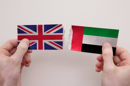 UK and UAE paper flags ripped apart. political relationship concept