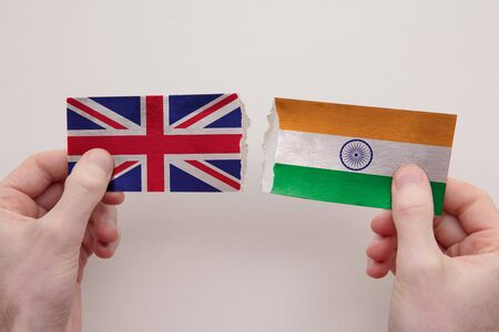 UK and India paper flags ripped apart. political relationship concept
