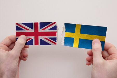 UK and Sweden paper flags ripped apart. political relationship concept