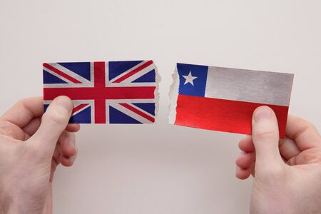 UK and Chile paper flags ripped apart. political relationship concept